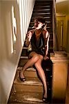 Hooker lighting cigarette while sitting on stairs in house