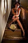 Portrait of hooker smoking cigarette on stairs in house