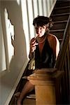 Portrait of hooker with cigarette sitting on stairs in house