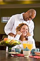 Laughing African American woman sitting at table having breakfast, man massaging shoulders    Stock Photo - Premium Rights-Managednull, Code: 842-02753718
