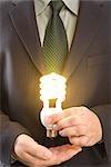 Businessman Holding Illuminated Energy Efficient Lightbulb