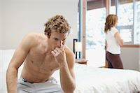 sad lovers break up - Man Sitting on Edge of Bed and Woman looking out Window in Background Stock Photo - Premium Royalty-Freenull, Code: 600-02757308