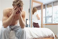 sad lovers break up - Man Sitting on Edge of Bed and Woman looking out Window in Background Stock Photo - Premium Royalty-Freenull, Code: 600-02757309