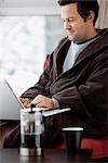 Man in Bathrobe Using Laptop Computer
