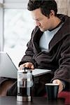 Man in Bathrobe Using Laptop Computer and Drinking a Cup of Coffee