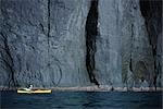 Person Boating on Kayak Near Cliff, Hokkaido, Japan