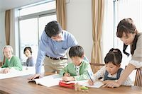Children doing homework with their parents Stock Photo - Premium Royalty-Freenull, Code: 622-02759191
