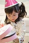 Asian girl opening her birthday present Stock Photo - Premium Royalty-Free, Artist: UpperCut Images, Code: 622-02759215