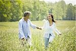 Mature man and a mid adult woman holding hands and running in a field Stock Photo - Premium Royalty-Free, Artist: Eyecandy Pro, Code: 640-02764597