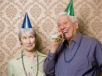 A senior man standing with a senior woman and blowing a party favor Stock Photo - Premium Royalty-Freenull, Code: 640-02764796