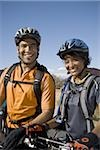 Man and woman with bicycles and helmets outdoors smiling Stock Photo - Premium Royalty-Free, Artist: Rommel, Code: 640-02765161