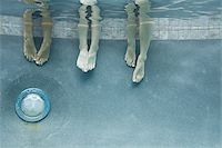 Low section view of three teenage girls feet in a swimming pool Stock Photo - Premium Royalty-Freenull, Code: 640-02766003