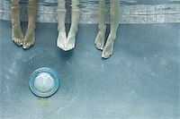 Low section view of three teenage girls feet in a swimming pool Stock Photo - Premium Royalty-Freenull, Code: 640-02766004