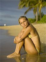 Portrait of a teenage girl sitting on the beach and hugging her knees Stock Photo - Premium Royalty-Freenull, Code: 640-02766245