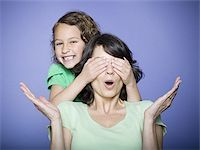 Close-up of a girl covering her mother's eyes Stock Photo - Premium Royalty-Freenull, Code: 640-02766977