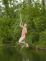 Portrait of a girl swinging on a rope Stock Photo - Premium Royalty-Freenull, Code: 640-02767080