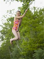 Portrait of a girl swinging on a rope Stock Photo - Premium Royalty-Freenull, Code: 640-02767081