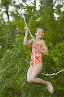 Portrait of a girl swinging on a rope Stock Photo - Premium Royalty-Freenull, Code: 640-02767088