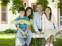 Portrait of a man and a woman smiling with their children Stock Photo - Premium Royalty-Freenull, Code: 640-02767192