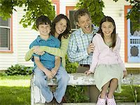 Portrait of a man and a woman smiling with their children Stock Photo - Premium Royalty-Freenull, Code: 640-02767193