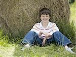 Portrait of a boy sitting against a hay bale Stock Photo - Premium Royalty-Free, Artist: Flowerphotos, Code: 640-02767232