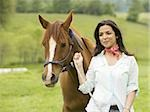 Portrait of a woman holding the reins of a horse Stock Photo - Premium Royalty-Freenull, Code: 640-02767466