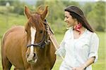 Portrait of a woman holding the reins of a horse Stock Photo - Premium Royalty-Freenull, Code: 640-02767468