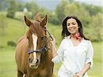 Portrait of a woman holding the reins of a horse Stock Photo - Premium Royalty-Freenull, Code: 640-02767469