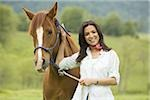 Portrait of a woman holding the reins of a horse Stock Photo - Premium Royalty-Freenull, Code: 640-02767470