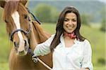 Portrait of a woman holding the reins of a horse Stock Photo - Premium Royalty-Freenull, Code: 640-02767472