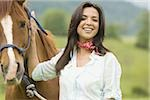 Portrait of a woman holding the reins of a horse Stock Photo - Premium Royalty-Freenull, Code: 640-02767473