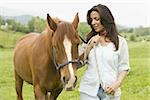 Portrait of a woman holding the reins of a horse Stock Photo - Premium Royalty-Freenull, Code: 640-02767474
