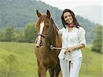 Portrait of a woman holding the reins of a horse Stock Photo - Premium Royalty-Freenull, Code: 640-02767475