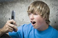 Close-up of a teenage boy using a mobile phone Stock Photo - Premium Royalty-Freenull, Code: 640-02767764
