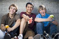 Portrait of three teenage boys eating fruit Stock Photo - Premium Royalty-Freenull, Code: 640-02767765