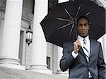Portrait of a male lawyer standing in front of a courthouse and holding an umbrella Stock Photo - Premium Royalty-Free, Artist: Robert Harding Images, Code: 640-02767783