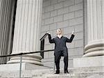 Low angle view of a male lawyer laughing and walking down the steps of a courthouse Stock Photo - Premium Royalty-Free, Artist: Robert Harding Images, Code: 640-02767819