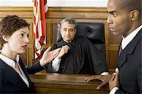 Two lawyers standing face to face in front of a male judge in a courtroom Stock Photo - Premium Royalty-Freenull, Code: 640-02767891