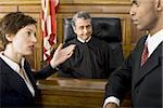 Two lawyers standing face to face in front of a male judge in a courtroom Stock Photo - Premium Royalty-Freenull, Code: 640-02767892