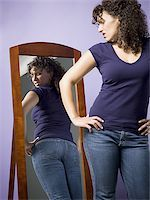 Young woman looking at her buttocks in the mirror Stock Photo - Premium Royalty-Freenull, Code: 640-02767899