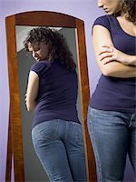 female rear end - Young woman looking at her buttocks in the mirror Stock Photo - Premium Royalty-Freenull, Code: 640-02767900