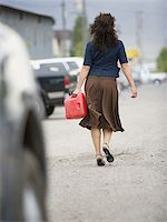 female rear end - Rear view of a young woman holding a gas can and walking Stock Photo - Premium Royalty-Freenull, Code: 640-02767918