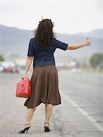 female rear end - Rear view of a young woman holding a gas can and hitchhiking Stock Photo - Premium Royalty-Freenull, Code: 640-02767919
