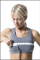 A young woman measuring her chest with a measuring tape Stock Photo - Premium Royalty-Freenull, Code: 640-02767983