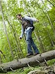 Low angle view of a young man walking on a fallen tree Stock Photo - Premium Royalty-Free, Artist: Robert Harding Images, Code: 640-02768281