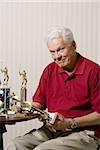 Portrait of a senior man holding a trophy Stock Photo - Premium Royalty-Free, Artist: foodanddrinkphotos, Code: 640-02768333