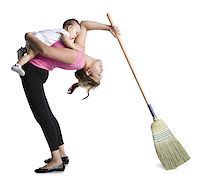 Contortionist mother sweeping while holding baby daughter Stock Photo - Premium Royalty-Freenull, Code: 640-02768497