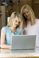 Young woman and mother working on laptop computer Stock Photo - Premium Royalty-Freenull, Code: 640-02768989