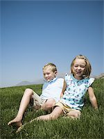 Boy and girl playing on a hill Stock Photo - Premium Royalty