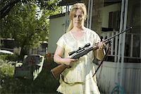 Woman in trailer park with a rifle Stock Photo - Premium Royalty-Freenull, Code: 640-02769453